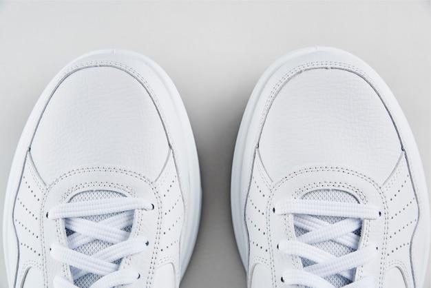 Paio di scarpe da ginnastica bianche su sfondo bianco Foto Premium