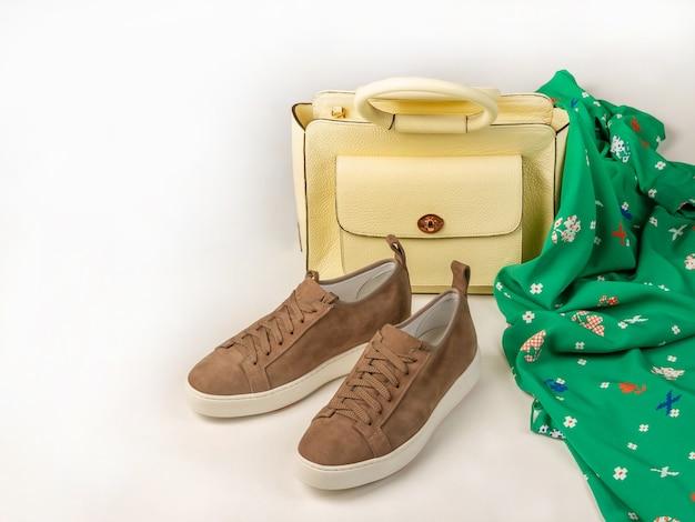 Un paio di sneakers da donna accanto a una borsa di pelle gialla e un vestito verde con una stampa elegante. su uno sfondo bianco. copia lo spazio a sinistra. vista laterale