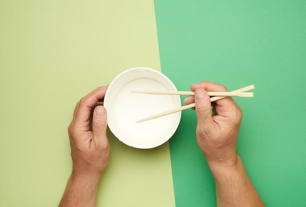 Coppia di bacchette di legno in una mano maschile e piatto di carta vuoto, vista dall'alto