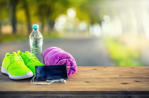 Coppia di scarpe sportive giallo verde acqua asciugamano smart pone e cuffie su tavola di legno. sullo sfondo il sentiero della foresta o del parco. accessori per la corsa sportiva.