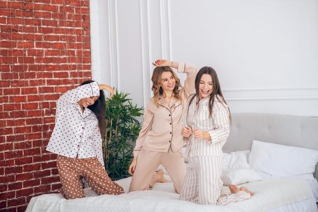 In pigiama. tre ragazze che hanno un pigiama party e si sentono allegre