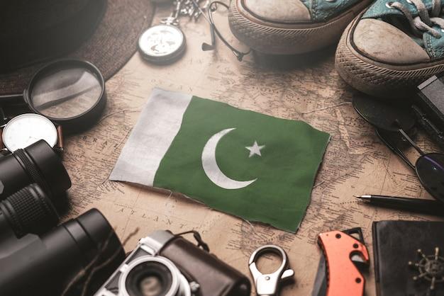 Bandiera del pakistan tra gli accessori del viaggiatore sulla vecchia mappa vintage. concetto di destinazione turistica.