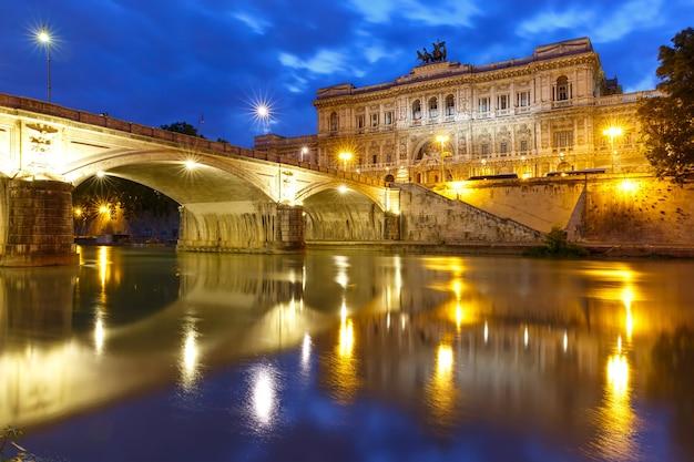 Il palazzo di giustizia e il ponte ponte umberto i con riflesso speculare visto dalla riva del tevere durante l'ora blu mattutina a roma, italia