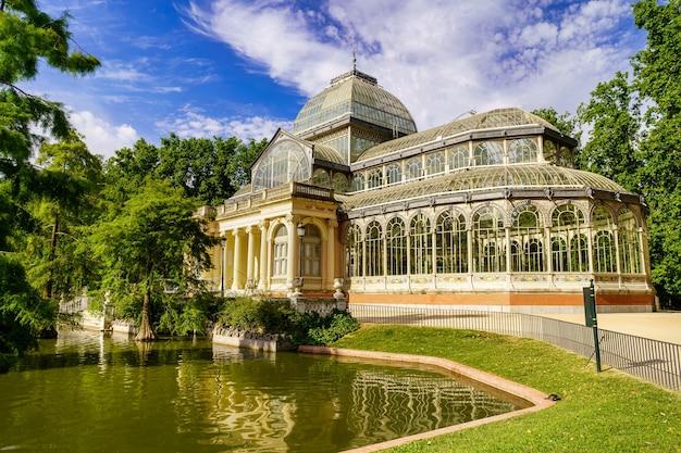 Palacio de cristal nel parco pubblico del retiro di madrid con il suo lago sulla facciata principale.