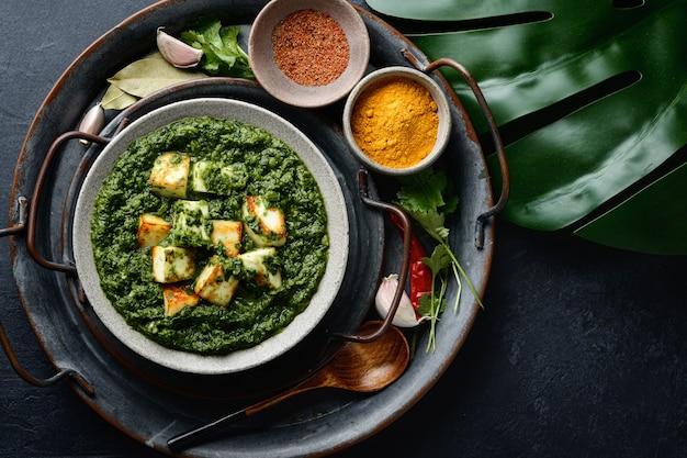 Cibo tradizionale indiano palak paneer con formaggio e spinaci su sfondo nero, vista dall'alto
