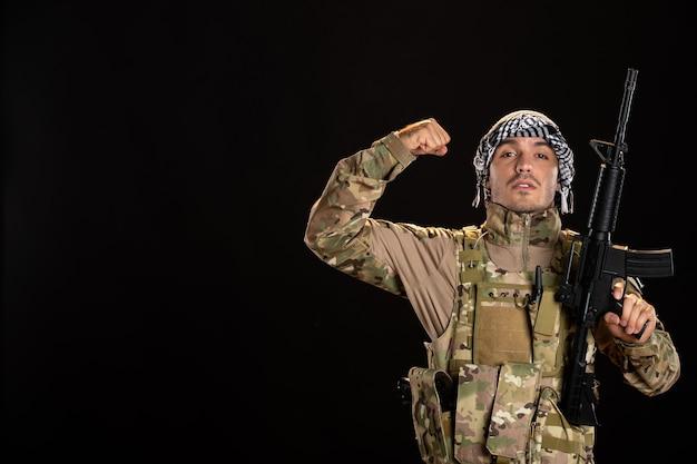 Soldato palestinese in mimetica che si flette sul muro nero