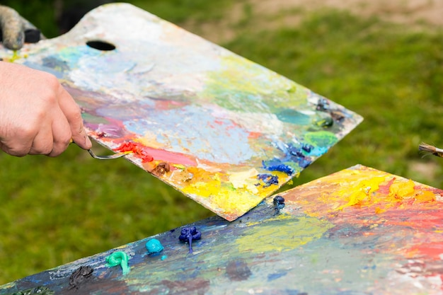 La spatola rimuove i residui di vernice da un'altra tavolozza