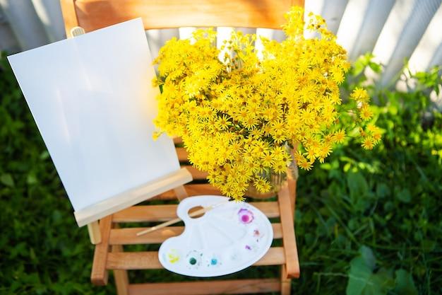 Una tavolozza di colori ad acquerelli multicolori si trova su una sedia di legno e un mazzo di fiori gialli, hobby creativo, disegno sulla strada.