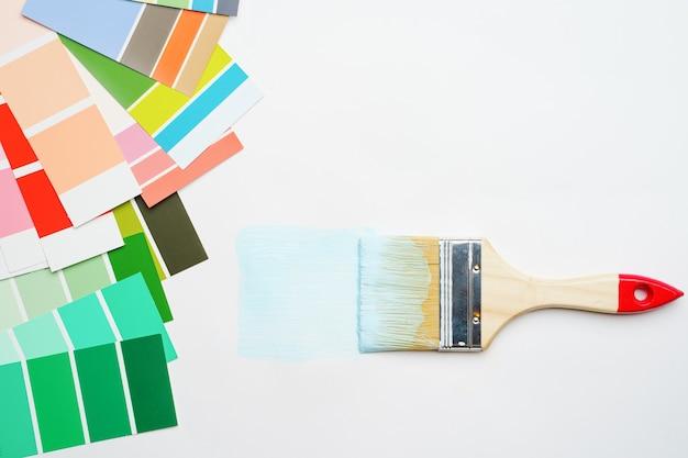 Tavolozza con colori blu e verdi, spazzole su sfondo bianco vuoto