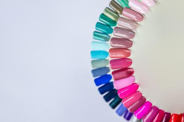 Tavolozza con i campioni di colore di smalto isolati su fondo bianco. diversi colori vivaci. pubblicità per campioni di manicure per smalto colorato. vista dall'alto della tavolozza ruota nail art. copia spazio