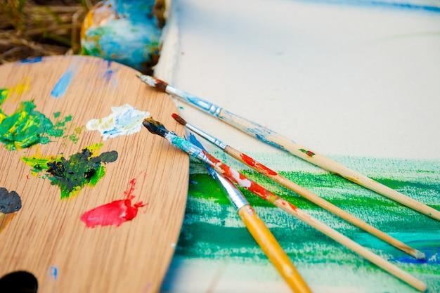 Tavolozza con colori e pennelli sulla foto su sfondo di erba.