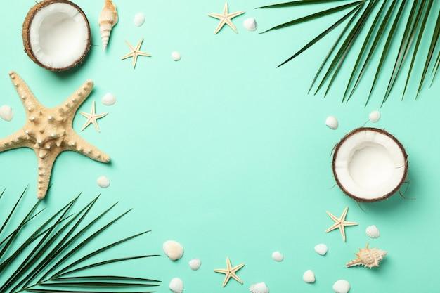 Rami di palma, stelle marine e cocco su superficie verde