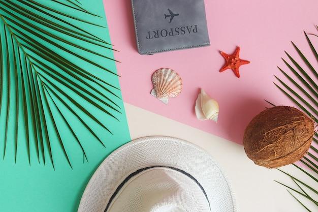 Foglie di palma cappello estivo cocco conchiglie e passaporto su una trama rosa verde e beige