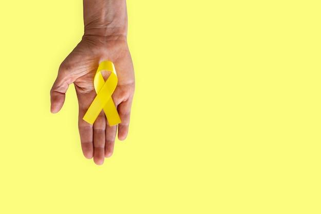 Palmo teso con nastro giallo della campagna di prevenzione del suicidio. settembre giallo.