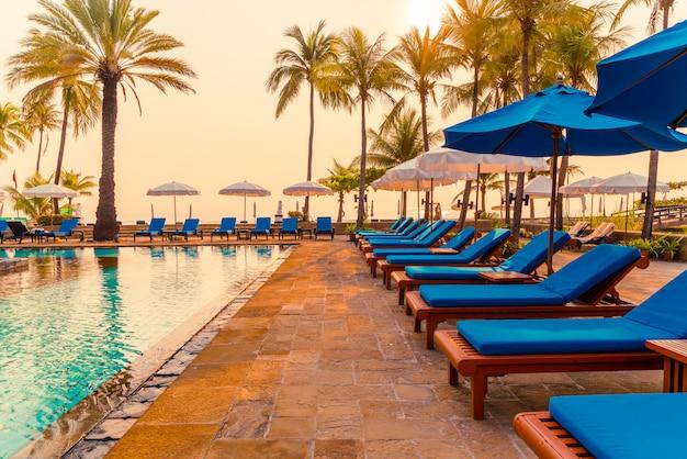 Palma con piscina con ombrellone in resort di hotel di lusso all'alba