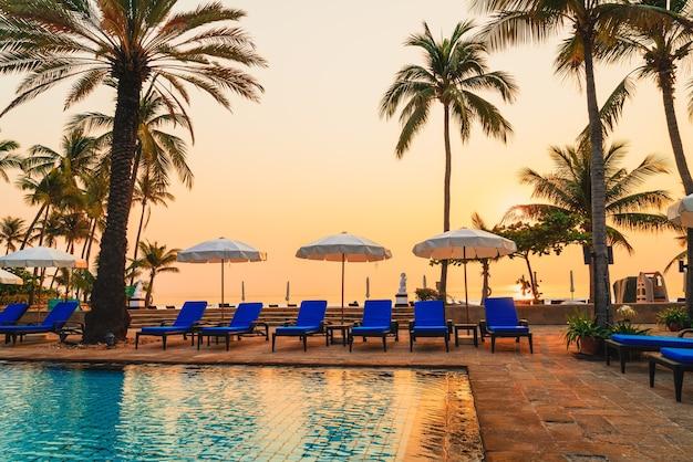 Palme con ombrelloni e sedie a bordo piscina nel resort di hotel di lusso all'alba