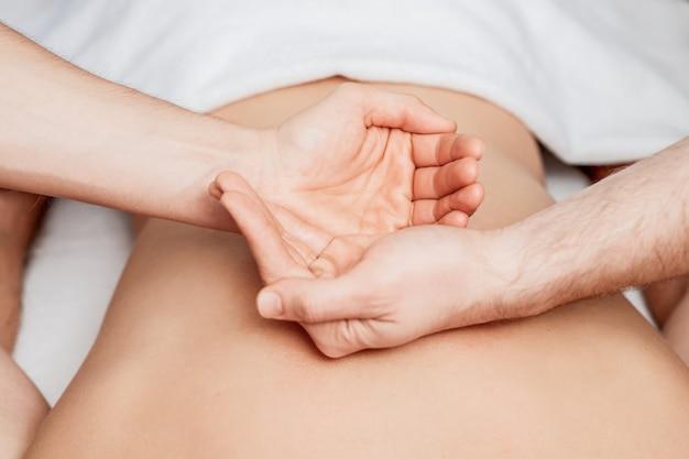 I palmi delle mani sulla schiena umana dal massaggiatore durante le mani mostrano yin e yang.