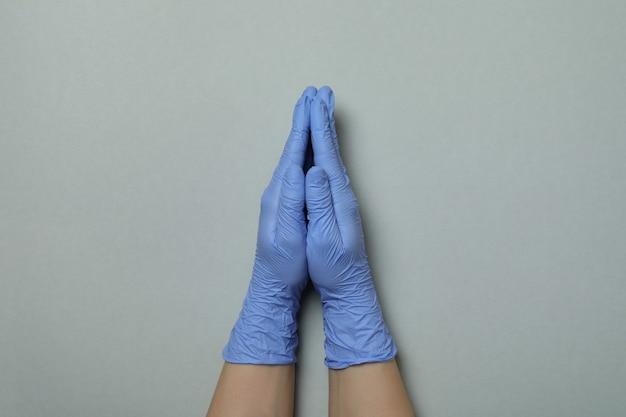 Palme in guanti medicali insieme su sfondo grigio chiaro isolato