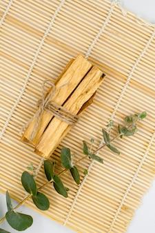 Bastoncini di legno di palo santo su stuoia di bambù con accessori per aromaterapia