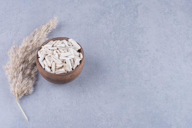 Erba della pampa e ciotola di semi di girasole, sul marmo.