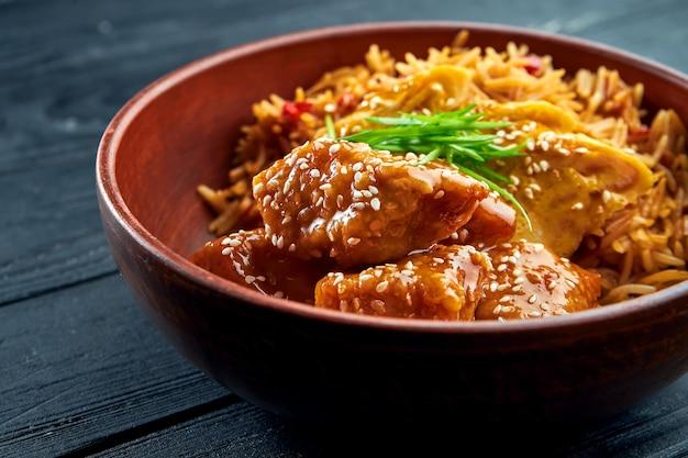Pan-asian street food - pollo in agrodolce guarnito con riso, servito in una ciotola su una superficie di legno. riso al wok con pollo. cibo asiatico. messa a fuoco selettiva