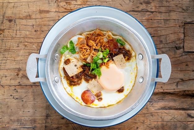 Pan fried egg topping con salsiccia tailandese su uno sfondo di legno
