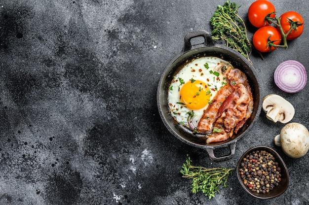 Pentola delle uova fritte con bacon e pomodoro fresco sull'insieme della prima colazione. tavolo nero.