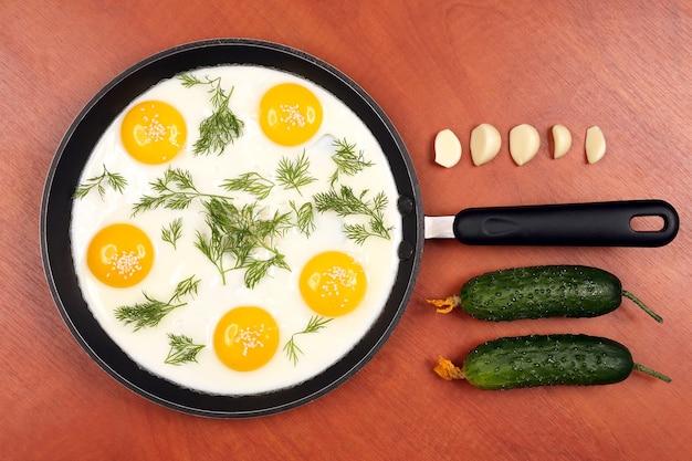 La padella sul tavolo con uova strapazzate fritte con aneto e cetriolo, aglio