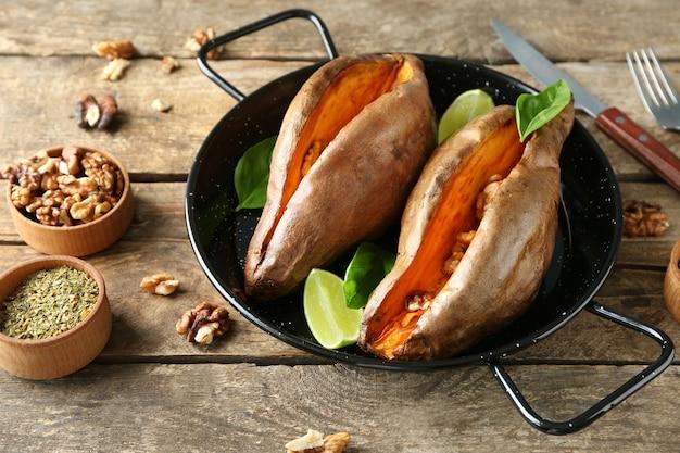 Padella con patate dolci al forno su tavola di legno wooden