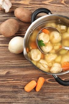 Pan con delizioso pollo e gnocchi sul tavolo di legno