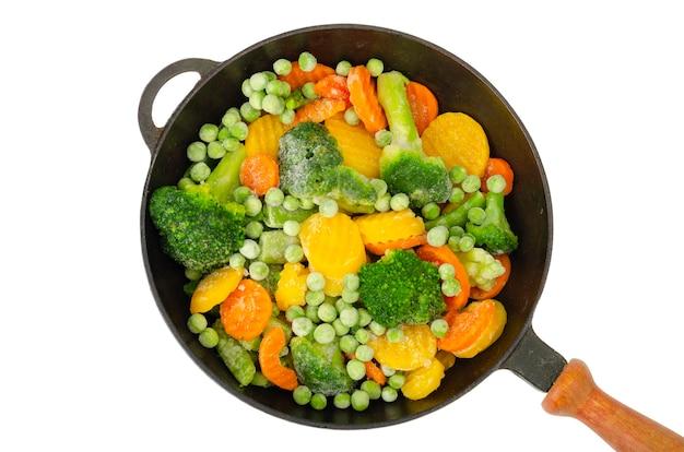 Padella con pezzi di verdure congelate isolato su bianco