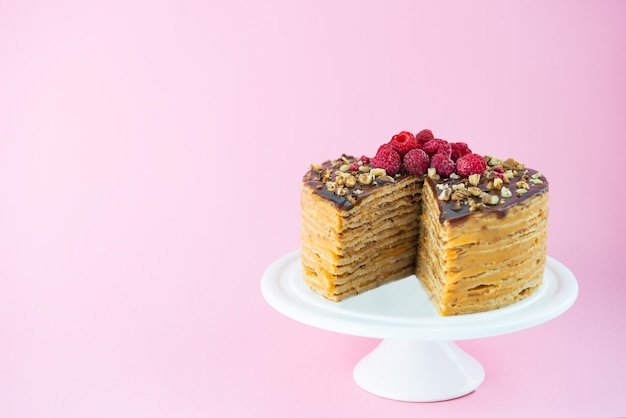 Torta frittella con noci caramellate al cioccolato e lamponi su una parete rosa