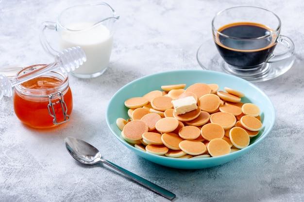 Pancake cereali con burro in una ciotola sul tavolo di pietra grigia.