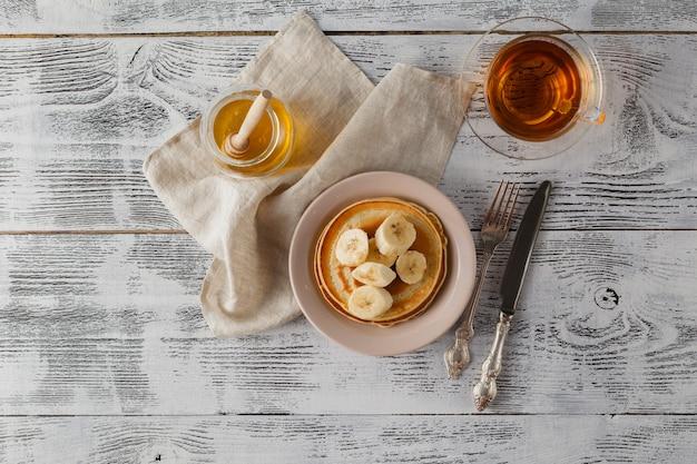 Pancake con banana, ricoperti di miele o sciroppo d'acero con spazio di copia