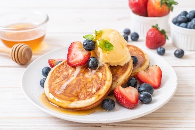 Pancake con mirtilli, fragole, miele e gelato alla vaniglia