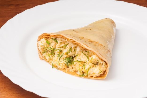Frittella con formaggio, aglio ed erbe aromatiche su un piatto bianco