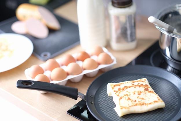 Pancake con ripieno delizioso che frigge in padella in primo piano della cucina