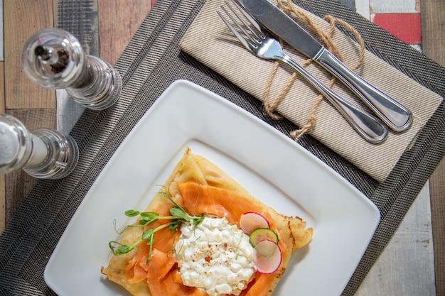 Pancake con salmone e sourcream e dille su un piatto bianco