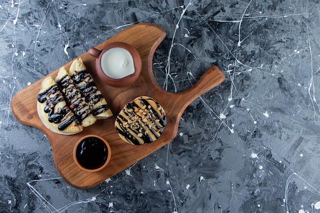 Frittelle e crepes con topping al cioccolato su tagliere di legno.