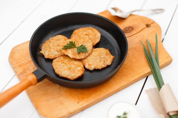 Frittelle di patate su una padella di ghisa con cipolle e prezzemolo