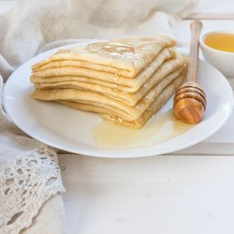 Pancake miele e cucchiaio di miele di legno su un piatto bianco con uno spazio di copia
