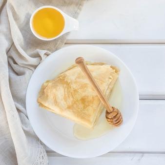 Pancake miele e cucchiaio di miele di legno su un piatto bianco