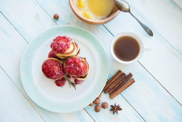 Frittelle, marmellata, miele, cannella e una tazza di caffè sul tavolo