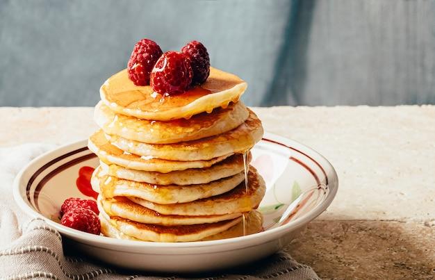 Pancake versati con miele decorato con lamponi su un piatto