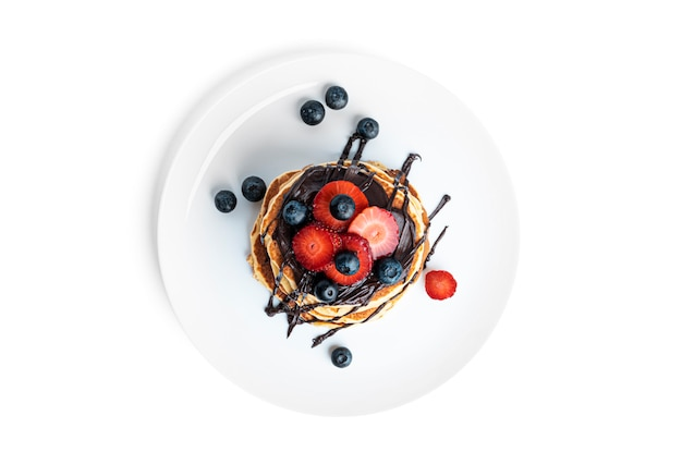 Frittelle con frutti di bosco e cioccolato isolato su bianco.