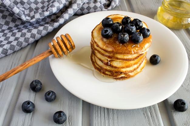 Frittelle con mirtilli e miele nel piatto bianco su fondo di legno grigio