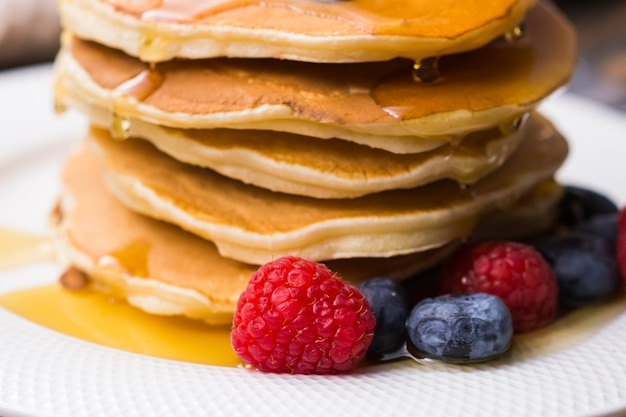Frittelle con mirtilli e lampone e sciroppo d'acero su fondo di legno. colazione e pasto tradizionale.