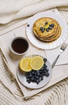 Pancake con il mirtillo e la protezione di caffè su un vassoio di legno su una base.
