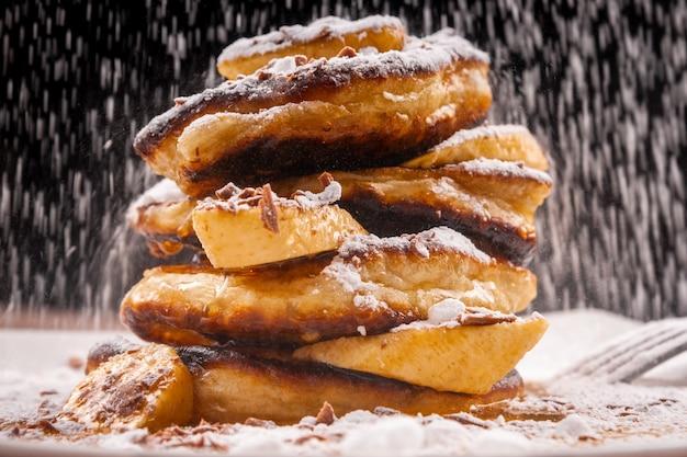 Pancake con cioccolato e banana e zucchero a velo che cadono sopra