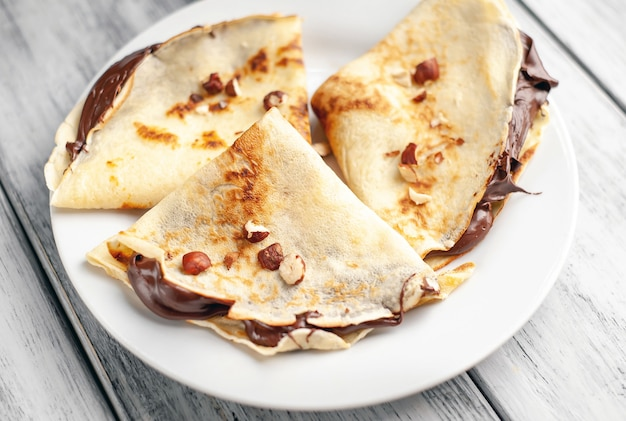 Pancake con crema spalmabile al cioccolato e nocciole, su un piatto bianco su uno sfondo di legno